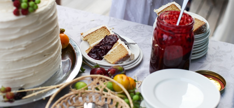 A simple, rustic wedding cake with fresh fruit and blackberry sauce