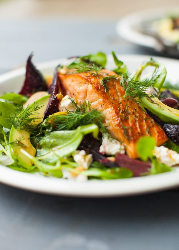 Warm salmon & spinach salad with roasted beets, avocado, feta and olives